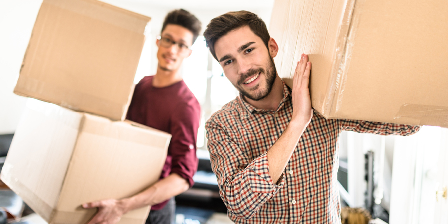 Men moving boxes into new home