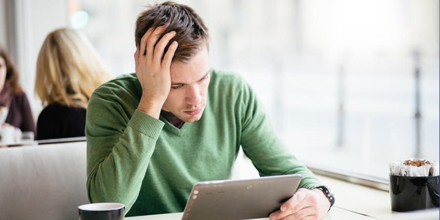 Worried man looks at tablet