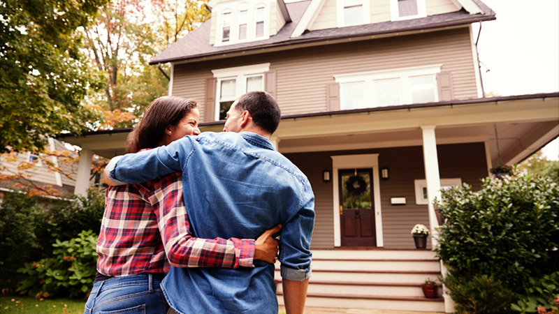 Happy couple embraces in front of their home
