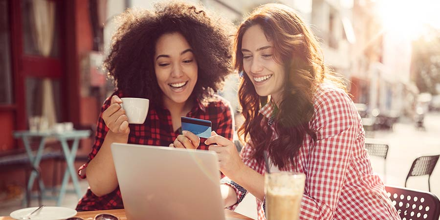 Two women talking about banking and technology over coffee