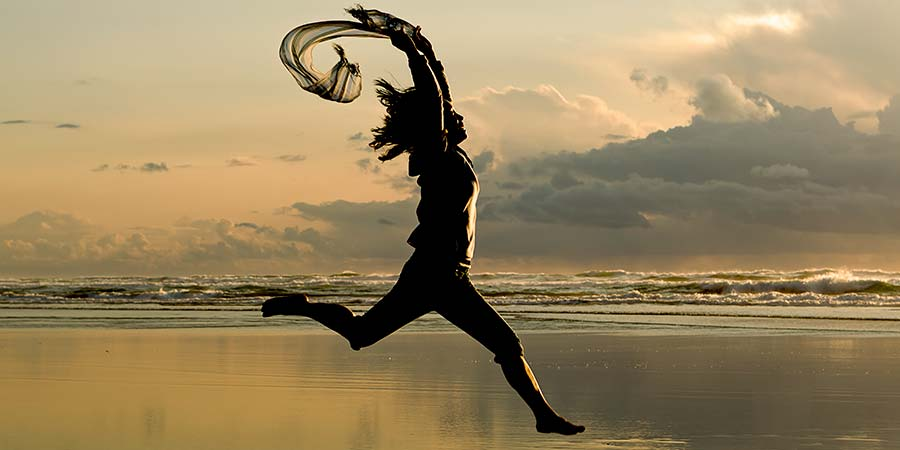 Woman leaping on a beach