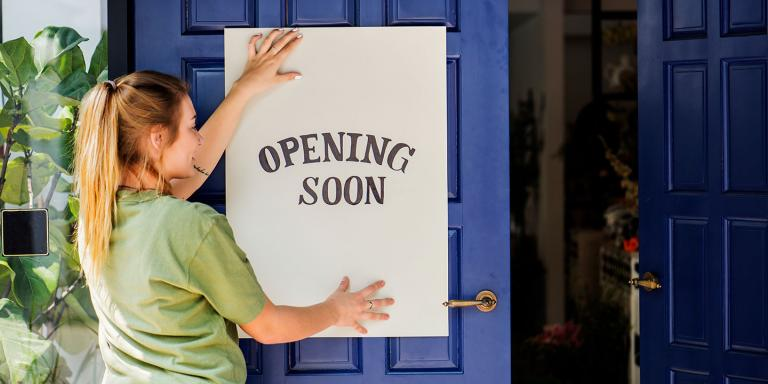 Woman placing an opening soon sign on her new business