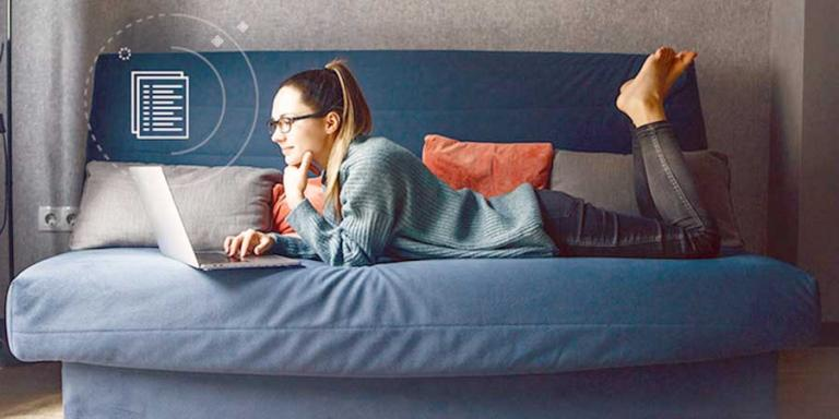 Young woman looking at her laptop while laying on a futon