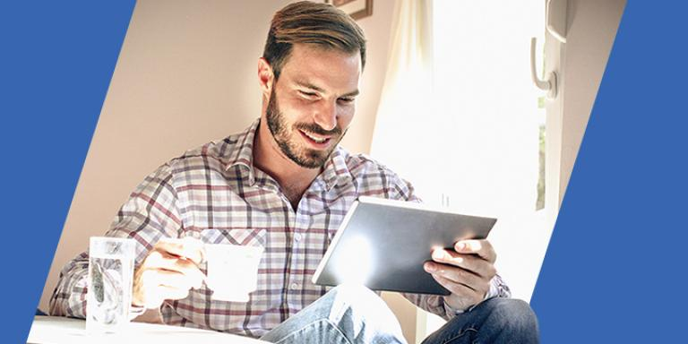 Bearded man sips tea while using Bill Pay to pay his bills on a tablet