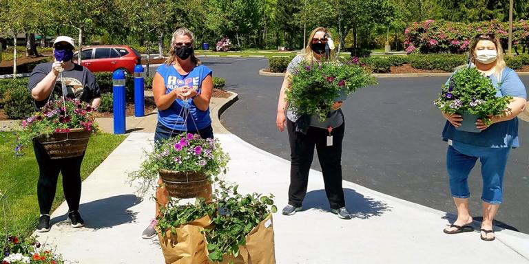 TwinStar Employees showing some hanging baskets from a recent plant sale fundraiser