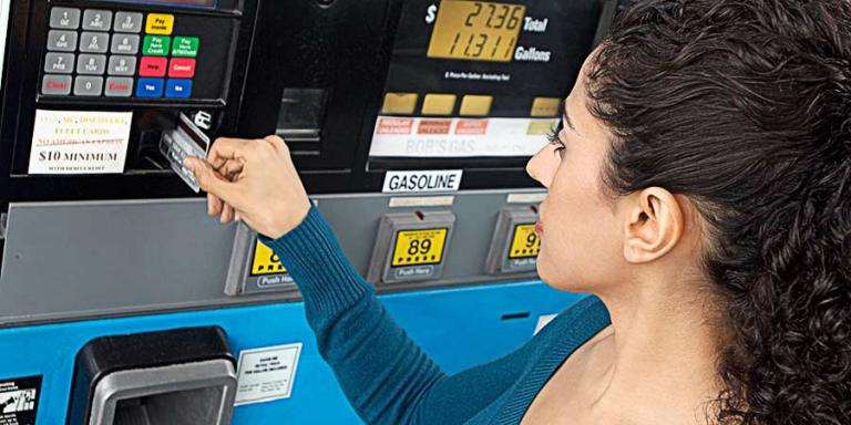 Woman paying at gas pump - stock image